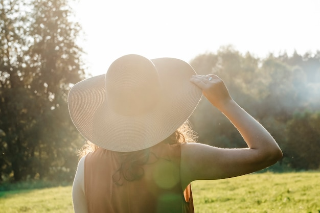 Happy girl in a hat enjoys life in a summer sunny field lifestyle summer relaxation travel concept h...