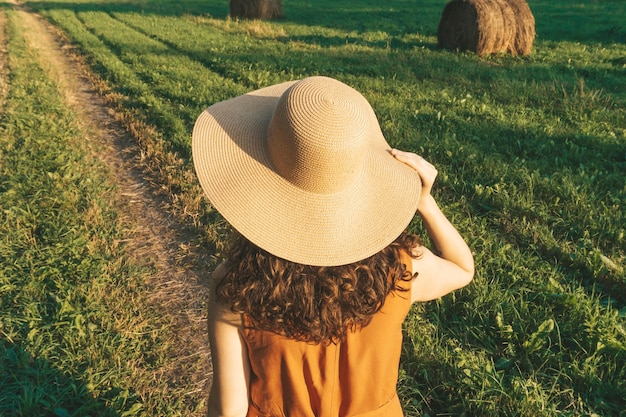 Happy girl in a hat enjoys life in a summer sunny field lifestyle summer relaxation travel concept