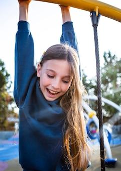 一人で遊び場で楽しんでいる幸せな女の子