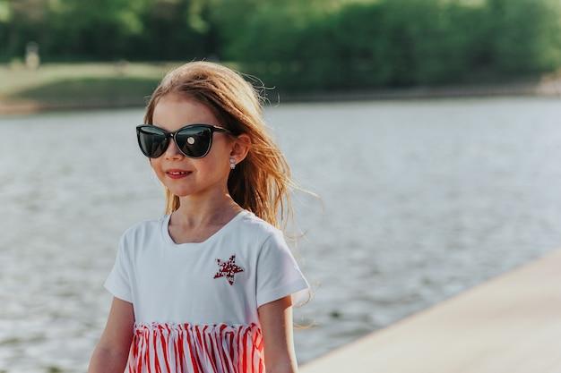 ウォーターフロントでサングラスを楽しんでいる幸せな女の子自然の自由の楽しみ