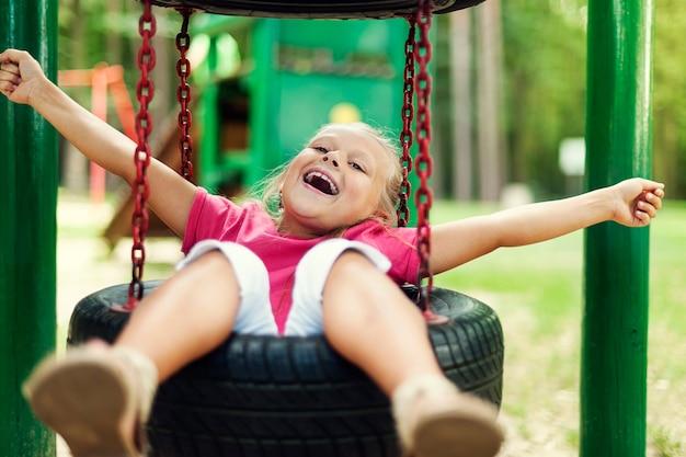 遊び場で楽しんで幸せな女の子