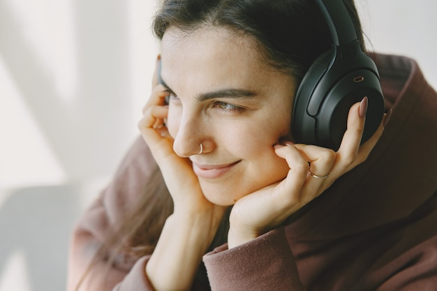La ragazza felice in cuffie ascolta la musica a casa