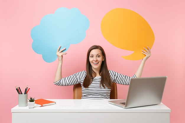 Happy girl hold blue yellow empty blank say cloud speech bubble work at white desk with pc laptop isolated on pastel pink background. achievement business career concept. copy space for advertisement.