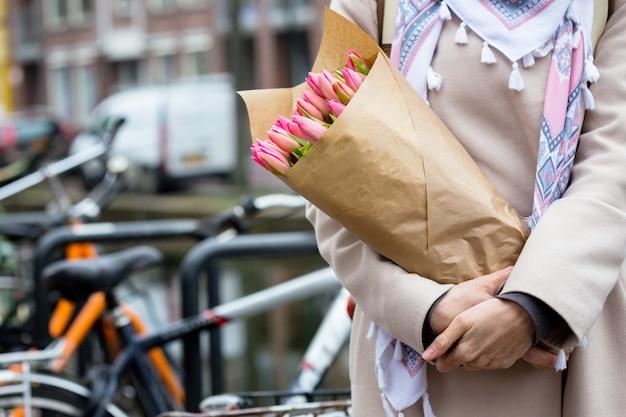 Счастливая девушка держит букет тюльпанов, стоя на улице амстердама. нидерланды