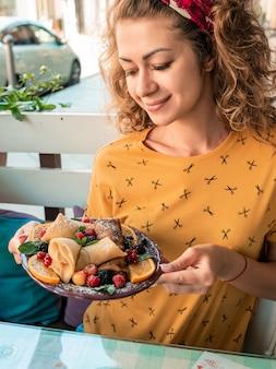 Счастливая девушка держит тарелку с блинами в руках. девушка заказала на завтрак блины с лесными ягодами. вкусный десерт на завтрак