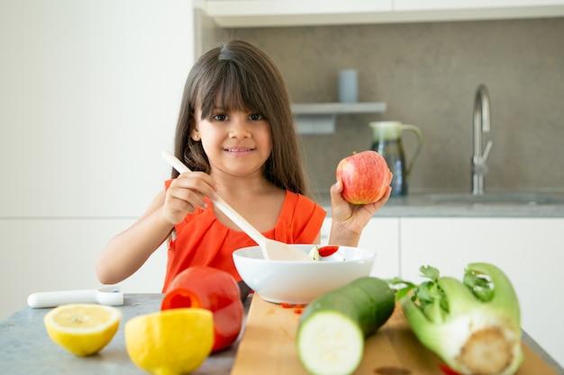 Счастливая девушка держит яблоко во время перемешивания салата в миске большой деревянной ложкой. милый ребенок учится готовить овощи на ужин. обучение приготовлению концепции