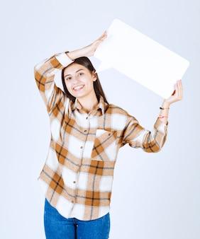 흰 벽에 빈 음성 프레임을 들고 있는 행복한 소녀.
