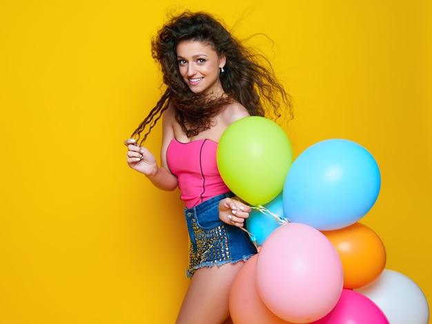 노란색 벽에 색된 공기 풍선을 들고 행복 한 여자