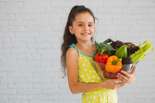 Happy girl holding colorful vegetable in glass bowl
