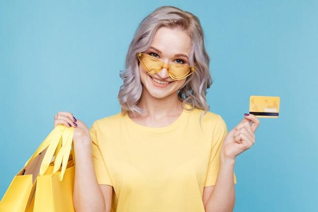 Счастливая девушка держит кредитную карту и большие хозяйственные сумки, изолированные над синей студией