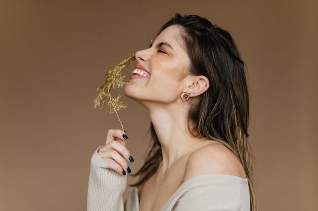 茶色の壁に花を保持している幸せな女の子。ポジティブな感情を表現する笑顔の魅力的な女性。