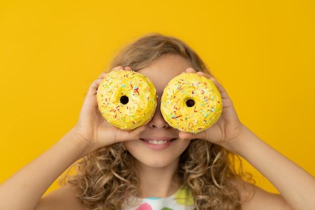 노란색 벽에 유약 된 도넛을 들고 행복 한 소녀입니다.