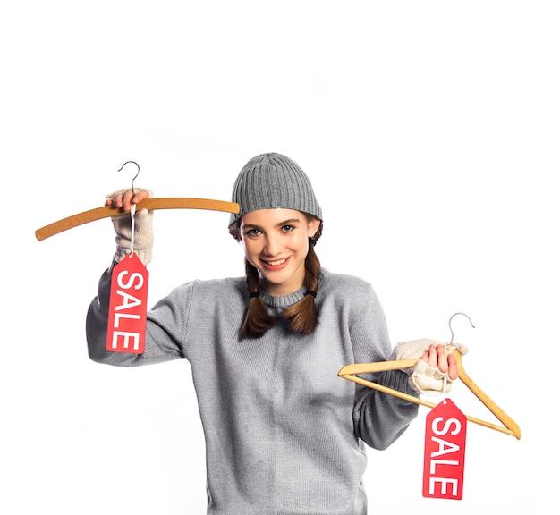 Счастливая девушка держит вешалки с ценниками продаж.