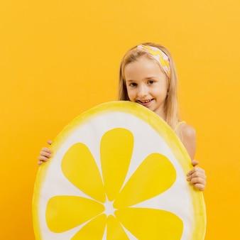 Счастливая девушка держит украшение ломтик лимона