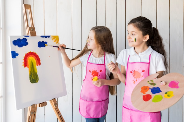 Happy girl holding palette in hand looking at her friend painting on the easel with paint brush