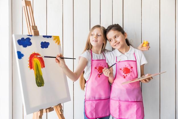 Счастливая девушка держит палитру в руке, глядя на ее подруга, рисующая на холсте кистью