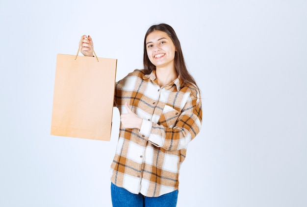 Happy girl holding paper craft package and giving thumbs up over white wall.