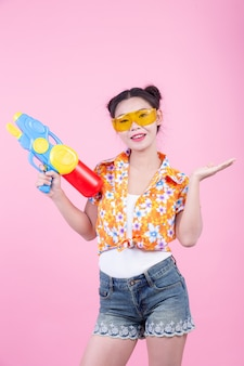 Happy girl holding a pink background water gun.