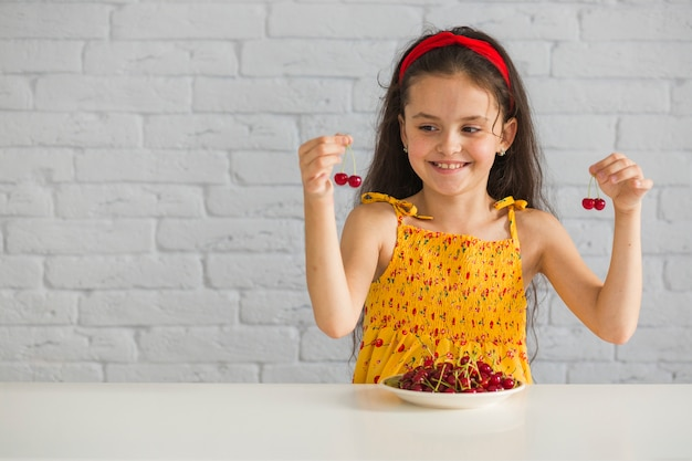 Happy girl holding red cherries on table against white brick wall
