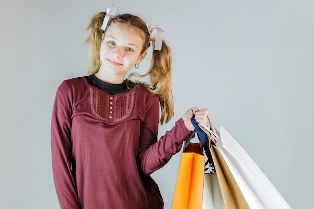 グレーの背景にショッピングバッグを持っている幸せな女の子