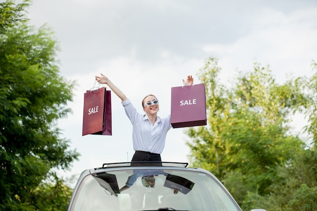 Happy girl holding the shopping packages in the car hatch, concept of discounts and shopping