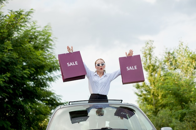 Happy girl holding the shopping packages in the car hatch, concept of discounts and shopping.