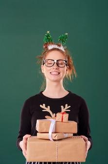 Ragazza felice che tiene pila di regalo di natale