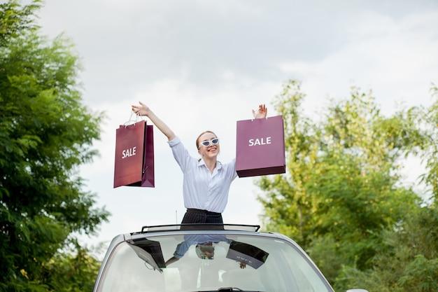車のハッチ、割引とショッピングの概念でショッピングパッケージを保持している幸せな女の子
