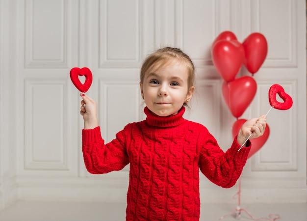 Счастливая девушка держит два сердца на палочке на белом фоне