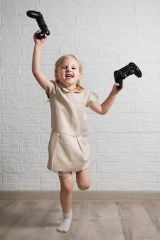 Счастливая девушка держит два джойстика