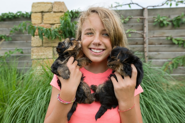 Happy girl holding two yorkshire terrier puppies