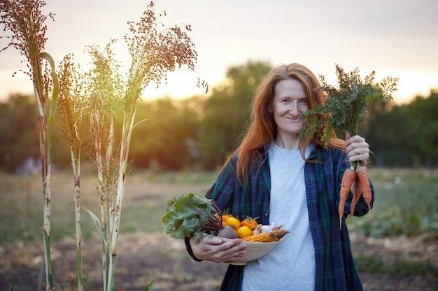 幸せな女の子はあなたの庭から野菜のボウルを保持します