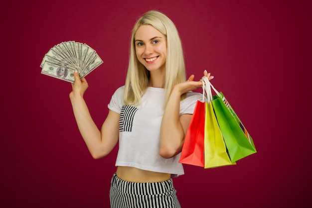 Happy girl in holds one hundred dollars bills and shopping bags on ruby background