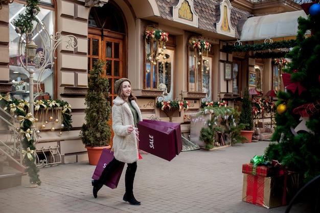 행복 한 소녀 크리스마스에 판매와 함께 상점에서 판매의 상징으로 종이 봉지를 보유하고있다.