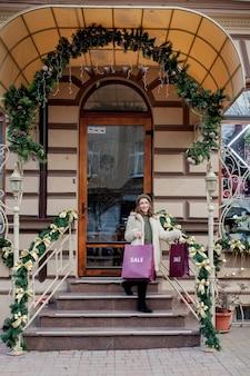 행복한 소녀는 도시 전역에서 크리스마스에 판매되는 상점에서 판매 상징이 있는 종이가방을 들고 있습니다. 쇼핑, 휴일, 행복, 크리스마스 판매의 개념.