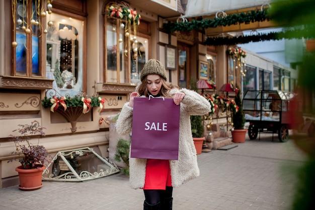 幸せな女の子は、街中のクリスマスに販売されている店で販売のシンボルが付いた紙袋を持っています。ショッピング、休日、幸福、クリスマスセールのコンセプト。