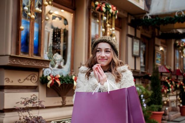 행복 한 소녀는 도시 주변 크리스마스에 판매와 함께 상점에서 판매의 상징으로 봉지를 보유하고있다. 쇼핑, 휴일, 행복, 크리스마스 판매의 개념.