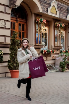 행복한 소녀는 도시 주변의 크리스마스에 판매되는 상점에서 판매 상징이 있는 종이가방을 들고 있습니다