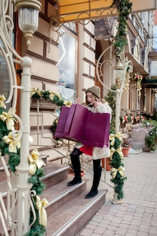 Счастливая девушка держит бумажные пакеты с символом продажи в магазинах с распродажами на рождество