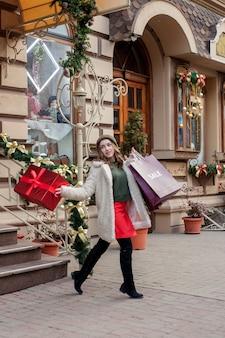 행복한 소녀는 크리스마스에 판매하는 상점에서 판매의 상징이 있는 종이가방을 들고 있다