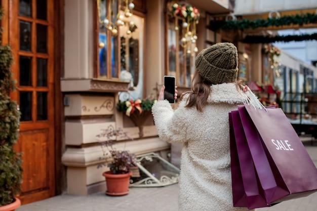 행복 한 소녀 크리스마스에 판매와 함께 상점에서 판매의 상징으로 종이 봉지를 보유