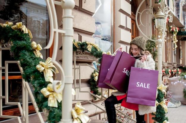 幸せな女の子は、クリスマスに販売の店で販売のシンボルと紙袋を保持します