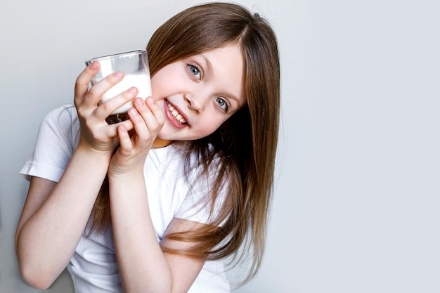 幸せな女の子は、透明なガラスから白い牛乳を保持します。