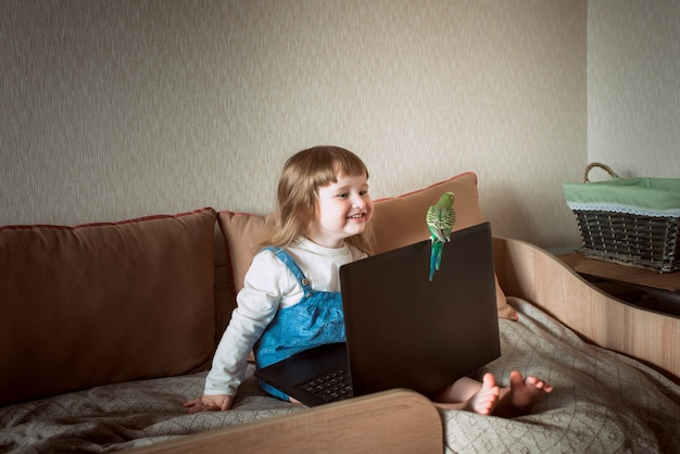 Happy girl at home. home pet. budgerigar. laptop and gadgets. baby watching cartoons, or online games.