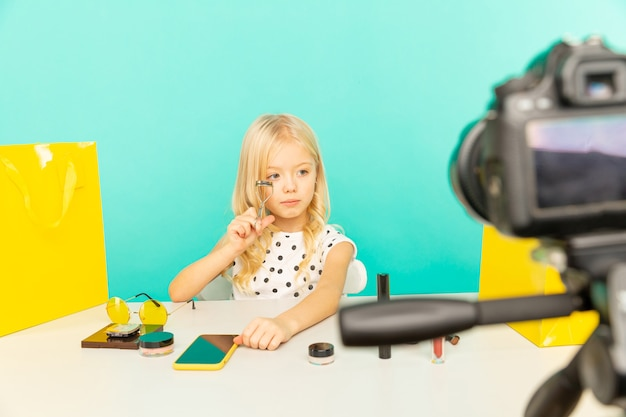 Happy girl at home speaking in front of camera for vlog. little kid working as blogger, recording video tutorial for internet.