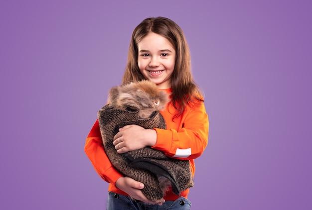 Счастливая девушка обнимает кролика, завернутого в ткань