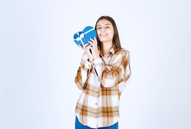La ragazza felice abbraccia il regalo a sorpresa sul muro bianco.