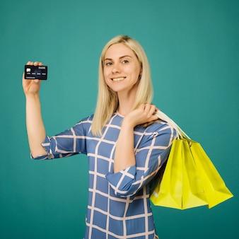 市松模様のブラウスの幸せな女の子は、青でクレジットカードとショッピングバッグを保持します