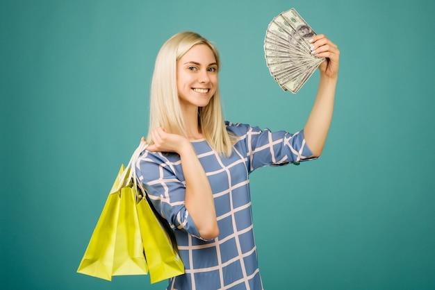 Счастливая девушка в клетчатой блузке держит купюры в сто долларов и сумки для покупок на синем фоне