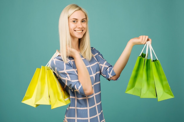 체크 무늬 블라우스에 행복 한 여자는 파란색에 쇼핑백을 보유 프리미엄 사진